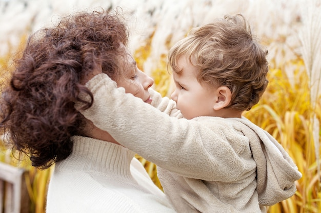 Happy mother and her little child in the park. child playing with mother's hair. mother and son embracing.