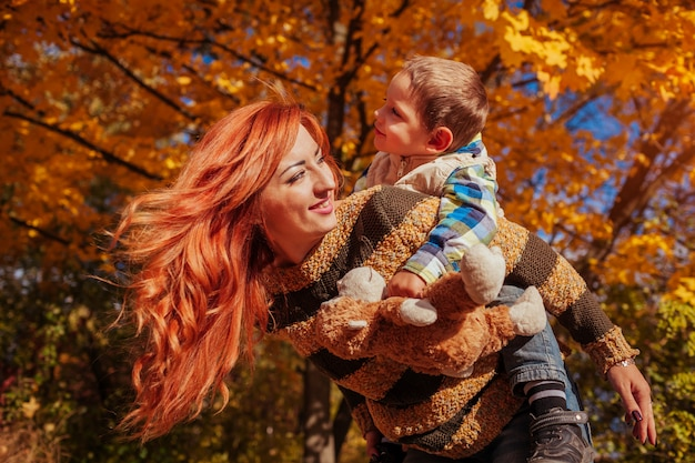 Happy mother and her little son having fun in autumn forest kid riding on mother's back