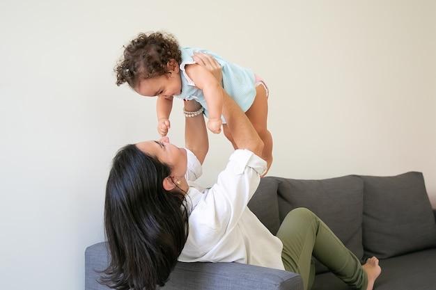 幸せな母親は、女の赤ちゃんを腕に抱き、自宅のソファに座って子供を持ち上げます。親子関係の概念