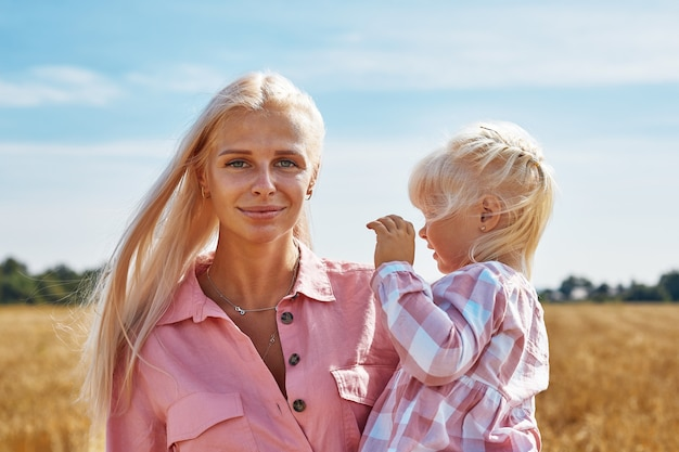 Счастливая мать, держащая ребенка, улыбаясь на пшеничном поле в солнечном свете.