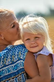 日光の下で麦畑で笑顔の赤ちゃんを抱いて幸せな母。