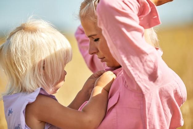 Счастливая мать держит ребенка, улыбаясь на пшеничном поле в солнечном свете