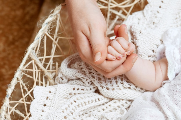 Happy mother holding hand of her newborn children