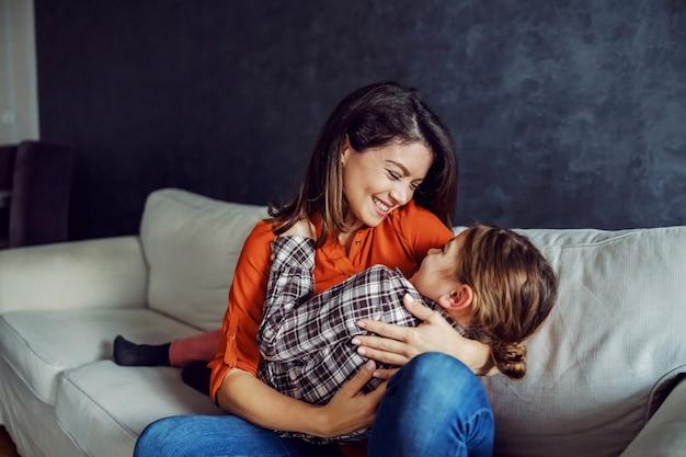 幸せな母親は娘を手に持って抱きしめています。