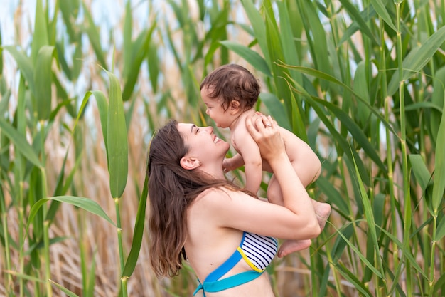 Happy mother holding her small baby girl, they play and laughing, summer time, on sea beach