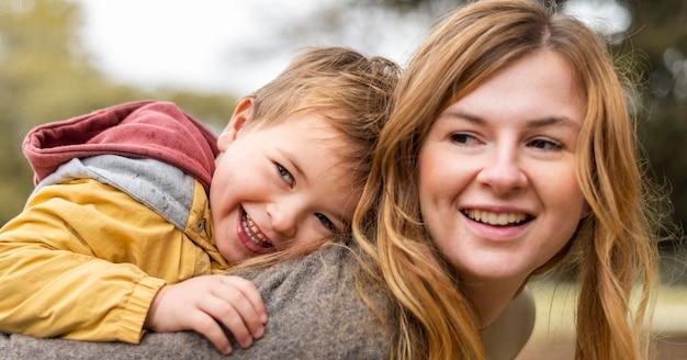 Счастливая мать держит ребенка на спине