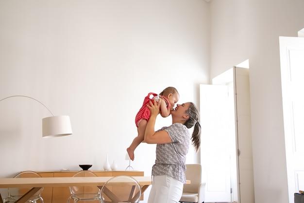 Madre felice che tiene bambina, alzandola e ridendo. neonata divertente divertendosi con mamma amorevole al chiuso e chiudendo il viso con le palme. tempo della famiglia, maternità e concetto di essere a casa