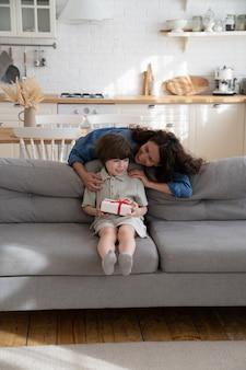 행복한 어머니는 포장된 선물 상자가 소파에 앉아 있는 밝은 유치원생 생일 소년을 껴안습니다.