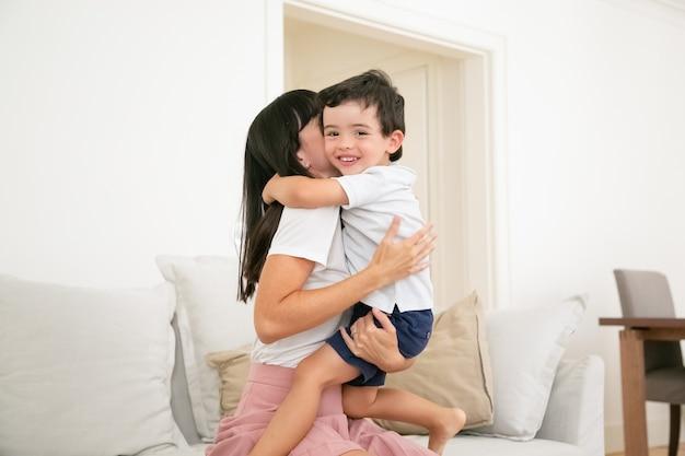 幸せな母が幼い息子を抱き締めて愛を込めてキスします。
