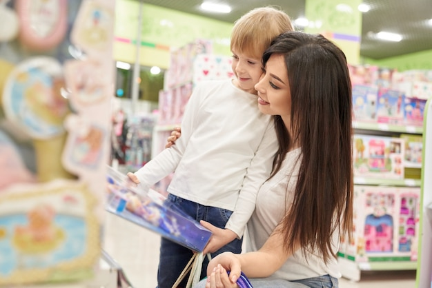 Happy mother hugging daughter and choosing doll in toy store