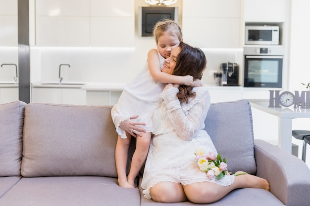 Happy mother hugging her cute little girl on sofa in living room