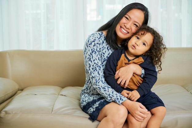 Счастливая мать, обнимая маленького ребенка