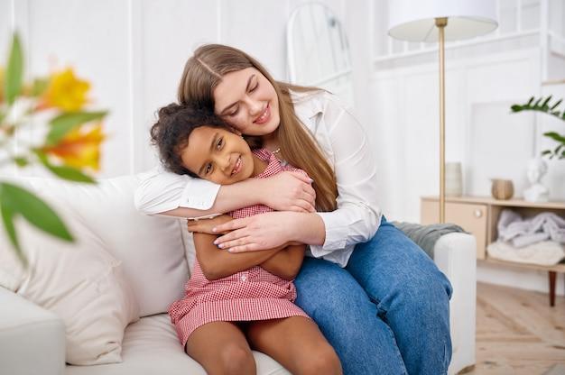 행복한 어머니는 거실에 있는 소파에 어린 딸을 안고 있습니다. 엄마와 여자 아이는 함께 집에서 여가를 즐기고, 좋은 관계, 부모의 보살핌