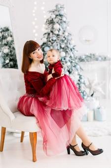 행복 한 어머니 드레스, 무릎에 작은 딸과 함께 앉아 크리스마스 시간을 즐기고