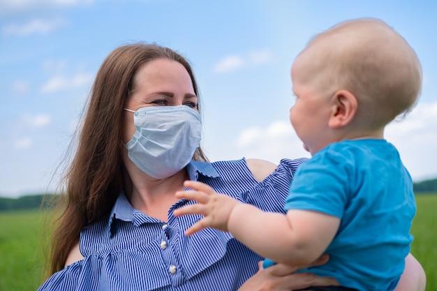 防護マスクで幸せな母が自然の中で腕に彼女の幼い息子を保持します