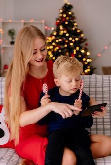 クリスマスツリーを背景に飾られた部屋で何かを示すスマートフォンとソファに座っている彼女の小さな子供と赤いドレスを着た幸せな母親