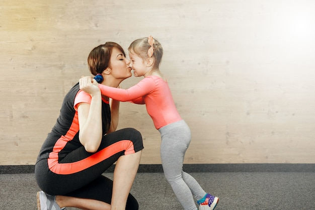 Happy mother kisses her daughter in the gym