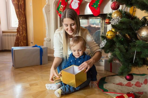 Счастливая мать, целуя своего маленького сына на елке