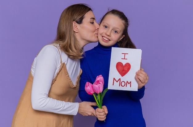 Madre felice che bacia la figlia sorridente e felice che tiene la cartolina d'auguri e i fiori dei tulipani che celebrano la giornata internazionale della donna in piedi sopra il muro viola