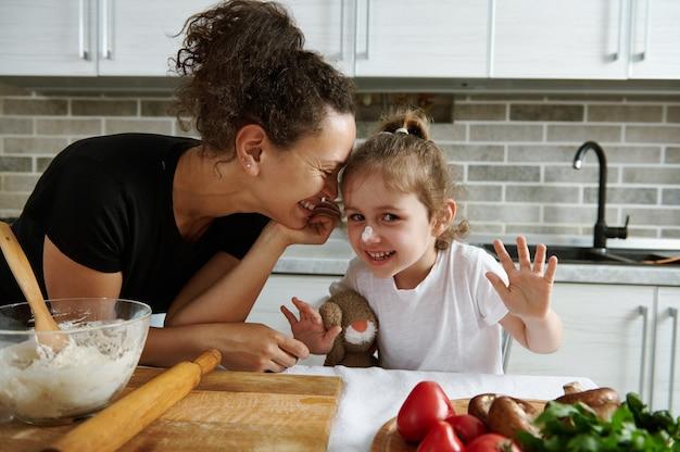 生地を作っている間、彼女の小さな娘にもたれて幸せな母親。母と娘が一緒に生地を準備します。愛、愛情、優しさ、女性の関係