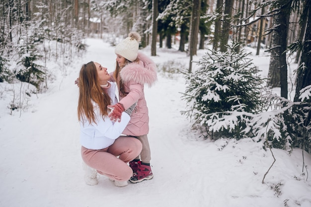 Happy mother and little cute girl in pink warm outwear walking having fun and hugging in snowy white