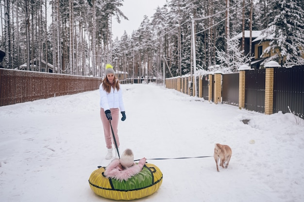 Happy mother and little cute girl in pink warm outwear walking having fun rides inflatable snow tube with red shiba inu dog in snowy white winter countryside outdoors