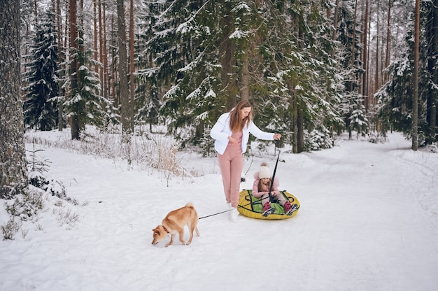 Happy mother and little cute girl in pink warm outwear walking having fun rides inflatable snow tube