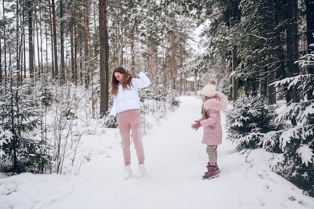 Happy mother and little cute girl in pink warm outwear walking playing snowball fight having fun in snowy white winter