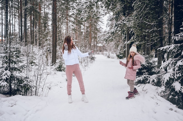 Happy mother and little cute girl in pink warm outwear walking playing snowball fight having fun