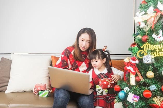 Madre felice e piccola figlia che decorano l'albero di natale e regali a casa
