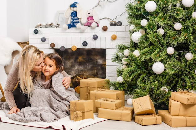 Happy mother and little daughter decorating christmas tree at home