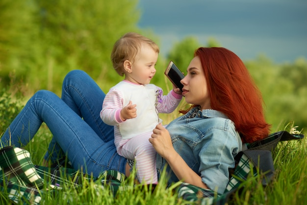 Happy mother and little daughter laying on green grass, child keeping cellphone.