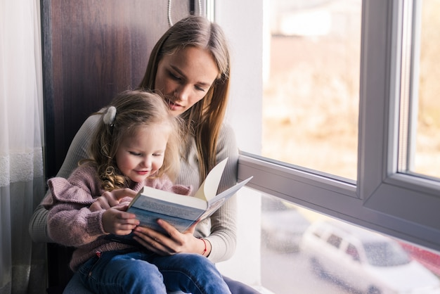 Happy mother and little daughter reading book, sitting on comfortable couch in living room