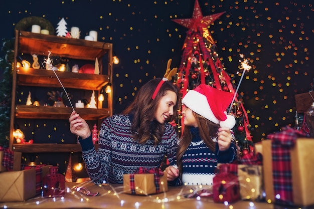 Happy mother and little girl in santa helper hat with sparklers in hands