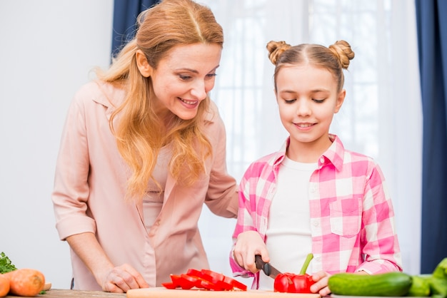 Happy mother looking at her daughter cutting the bell pepper with knife on chopping board