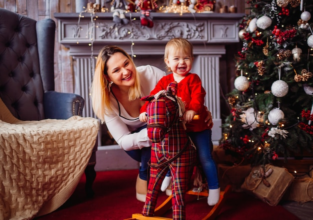 Happy mother and lovely child on the toy horse pose before a christmas tree