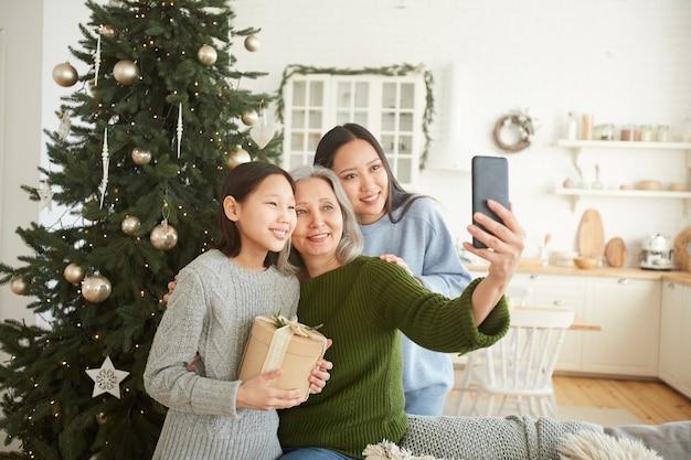 Счастливая мать делает селфи портрет на мобильном телефоне вместе со своими двумя дочерьми во время рождества