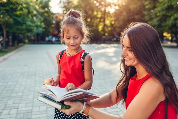 Happy mother met her daughter after classes outdoors primary school.