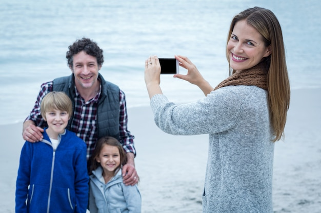 Happy mother photographing family at beach