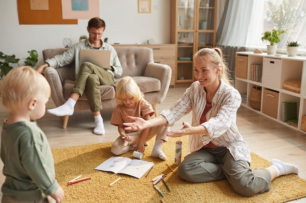 Happy mother playing on the floor together with her children while father working on laptop sitting on sofa at home