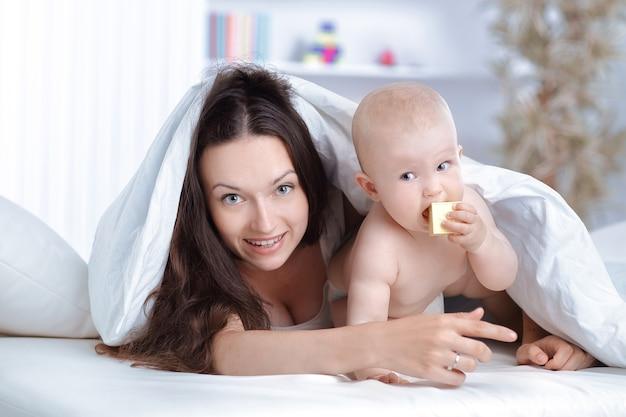 幸せな母親は、ベッドに横たわっている赤ちゃんと遊ぶ。教育の概念