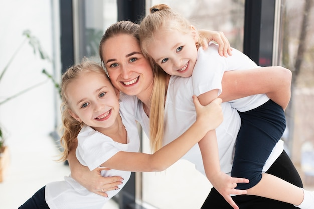 Happy mother posing with daughters at home