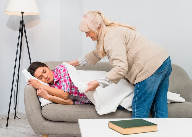 Happy mother putting white blanket over her daughter sleeping on sofa at home
