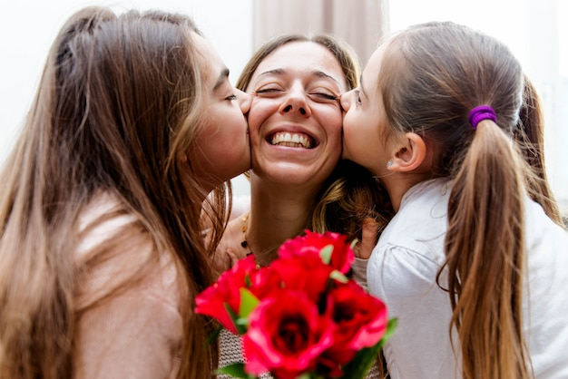 Happy mother receiving a gift from her daughters in living room