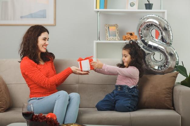幸せな母は彼女の小さな子供の娘からプレゼントを受け取ります。 3月8日国際女性の日を祝う