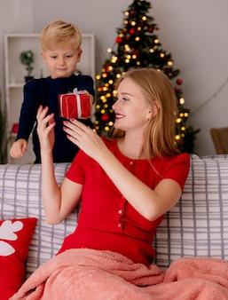 Madre felice in abito rosso seduto su un divano sorridendo mentre il suo bambino in piedi dietro fa un regalo a sua madre in una stanza decorata con albero di natale sullo sfondo