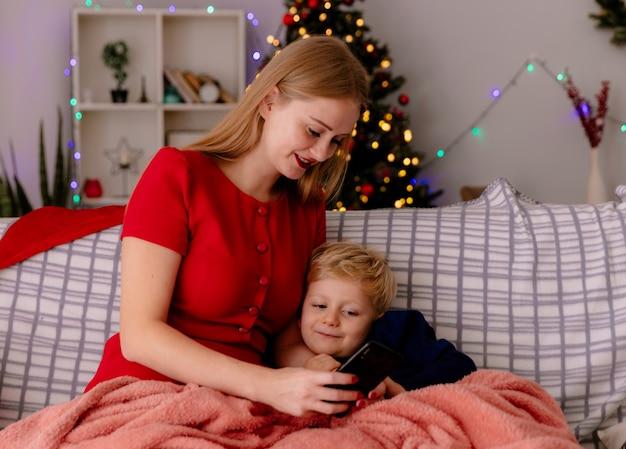 Madre felice in abito rosso seduta su un divano con il suo bambino sotto la coperta con smartphone in una stanza decorata con albero di natale nel muro