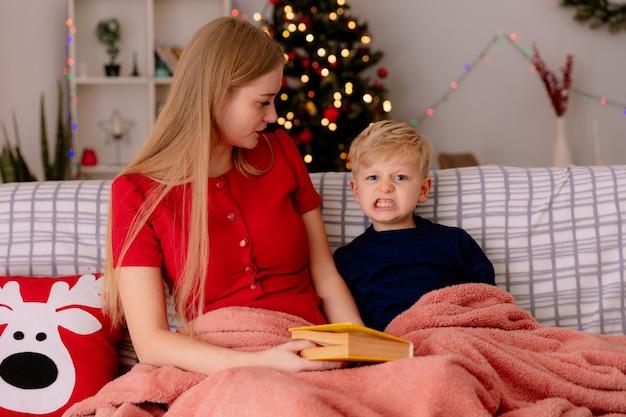 Madre felice in abito rosso con il suo bambino sotto la coperta con un libro che legge in una stanza decorata con albero di natale nel muro