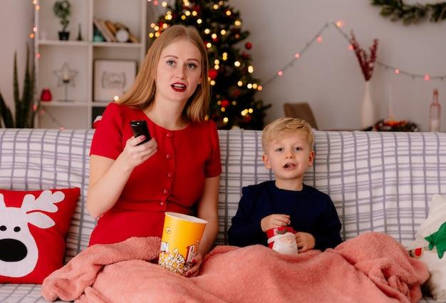 Felice madre in abito rosso con il suo bambino seduto su un divano sotto la coperta con un secchio di popcorn guardando la tv insieme in una stanza decorata con albero di natale sullo sfondo