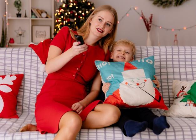 Felice madre in abito rosso con il suo piccolo bambino seduto su un divano divertendosi a guardare la tv insieme in una stanza decorata con albero di natale in background